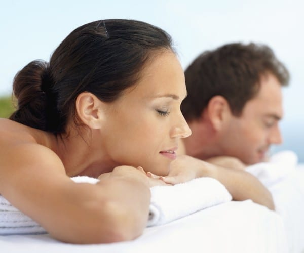 Portrait of an attractive young couple lying on massage bed at spa